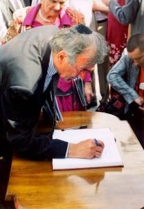 Elie Wiesel semnează  în cartea de impresii