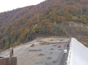 Muncitorii lucrează la umplerea corpului barajului Runcu